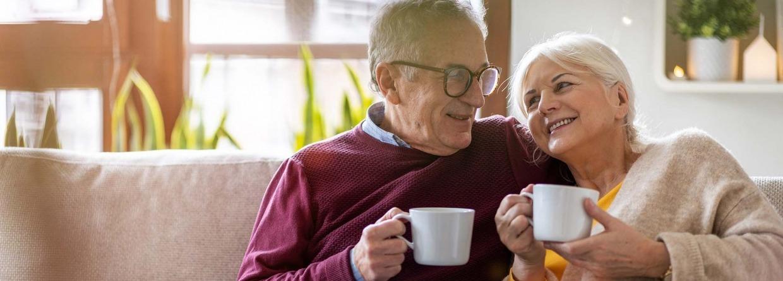 Gelukkig senior paar thuis op de bank met een kop koffie