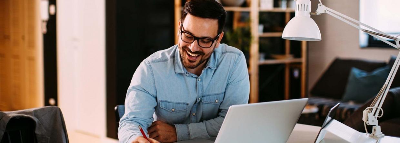 Jonge zakenman die thuis werkt met laptop en papieren op bureau