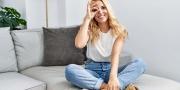 Blonde vrouw zittend thuis op de bank doet ok gebaar en kijkt door vingers met blij gezicht